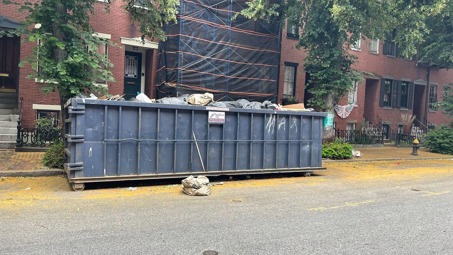 Overflowing dumpster and it's taking up twice the permitted space.