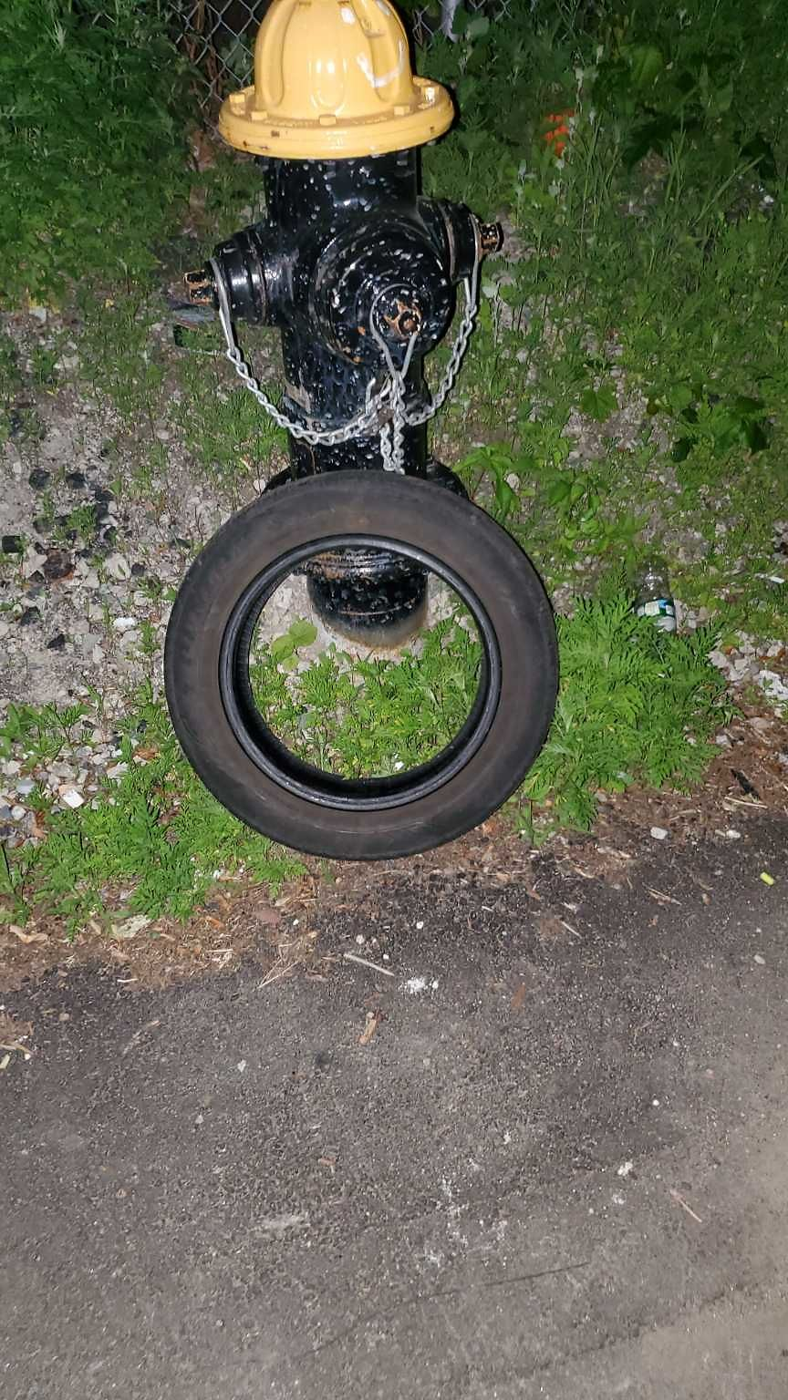 Trash tire across from 17 Balina against hydrant