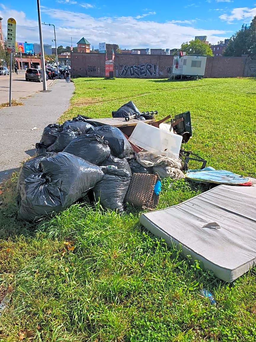 Please remove large amount of yard waste and trash on sidewalk next to bus Stop on the corner of Blue Hill and Crawford street. No code enforcement violation found at this time.