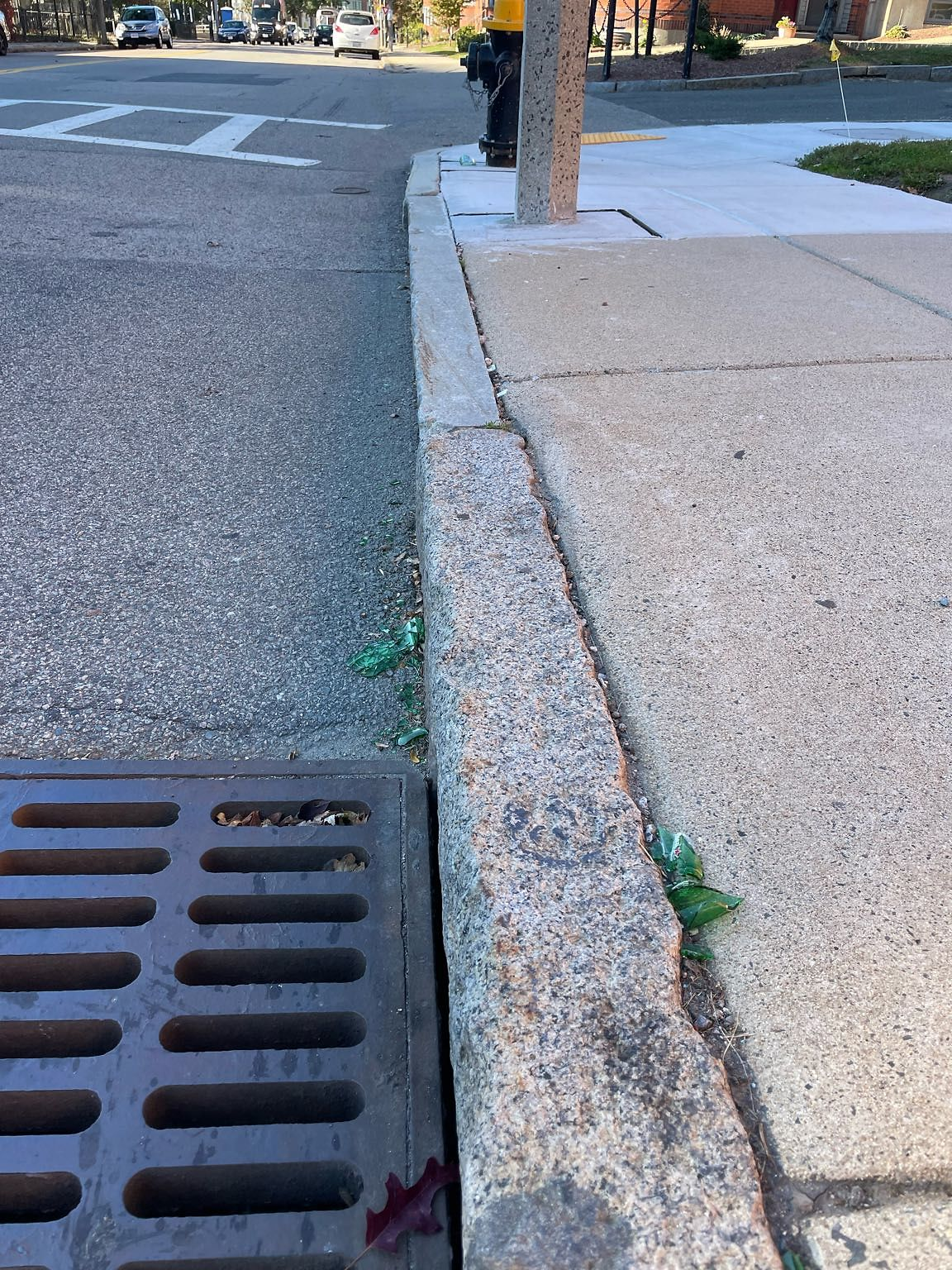 Broken glass bottle shards on curb and in gutter from here to fire hydrant